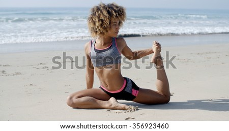 Young woman in yoga pose on the beach slow motion - stock photo