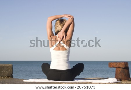 Young woman in yoga position next to the sea