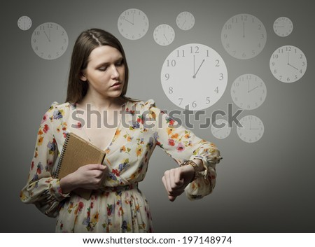 Young woman indicating her wristwatch and 1 p.m. - stock photo
