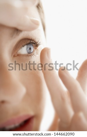 Young woman inserting contact lens isolated on white background - stock photo