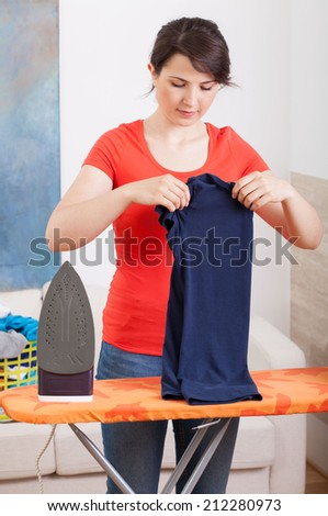 Young woman ironing and folding clothes, vertical