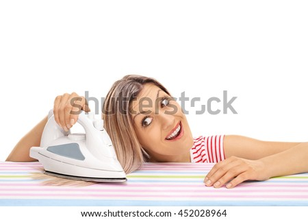 Young woman ironing her hair with an iron isolated on white background - stock photo