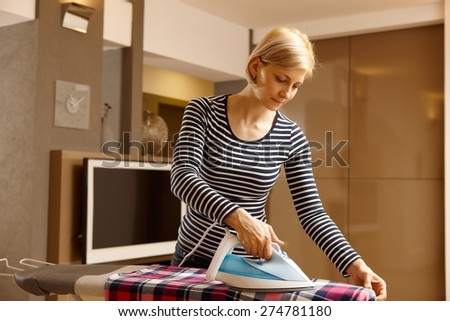 Young woman ironing in living room at home. - stock photo