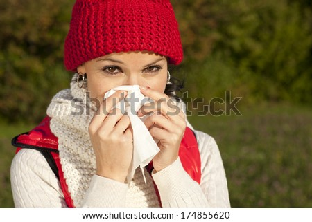 Young woman is blowing her nose outdoor