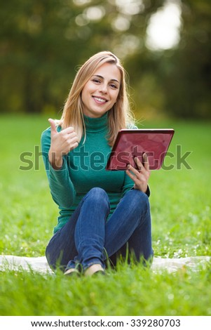 Young woman is chatting with her friend by using digital tablet in park