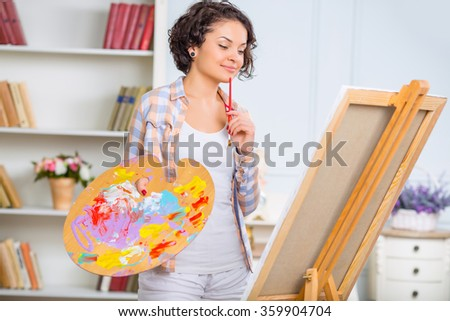 Young woman is checking her piece of art. - stock photo