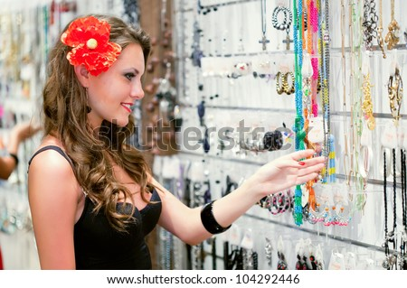 Young woman is choosing jewelry in the shop