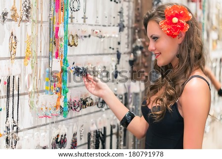 Young woman is choosing jewerly in the shop - stock photo