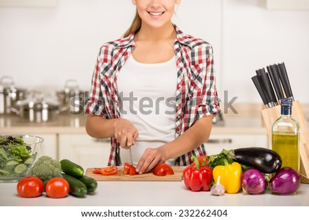 Young woman is chopping vegetables in the kitchen.