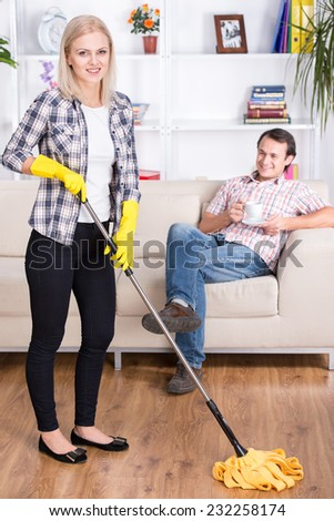 Young woman is cleaning floor, while husband drinking coffee on sofa at home. - stock photo