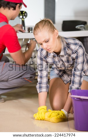 Young woman is cleaning the floor in the bathroom, while plumber repairs the pipes. - stock photo