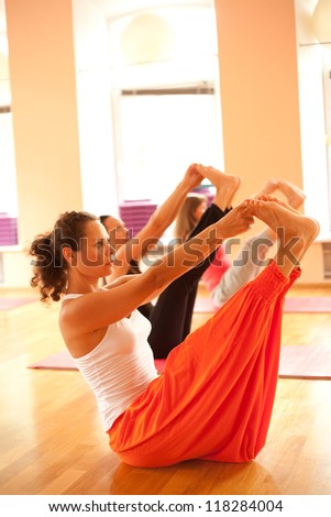 Young woman is doing yoga at sport club - stock photo