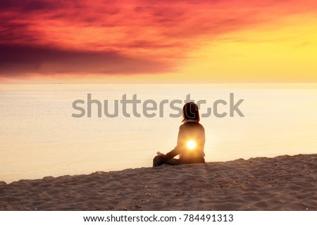 Young woman is doing yoga on the beach, inner light concept, spiritual background, double exposure