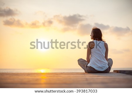Young woman is doing yoga on the sunrise background.