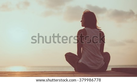 Young woman is doing yoga on the sunrise background. Artistic toning.