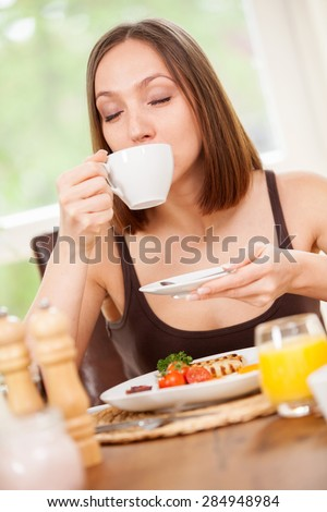 Young woman is drinking a hot cup of coffee while having a breakfast at home - stock photo