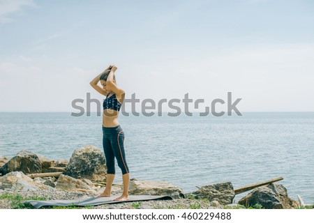 young woman is engaged in meditation, stretching, yoga on the beach background