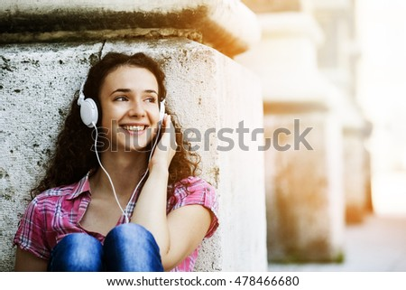 Young woman is enjoying outside and listening music.