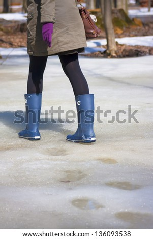 Young woman is going by the spring snow in a rubber boots.