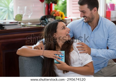 Young woman is happy and surprised with a gift from her husband - stock photo