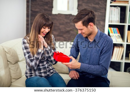 Young woman is happy and surprised with a gift from her husband, boyfriend. - stock photo