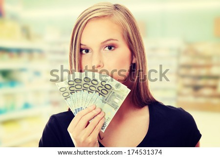 Young woman is holding euro bills and covering mouth. In shoop. - stock photo