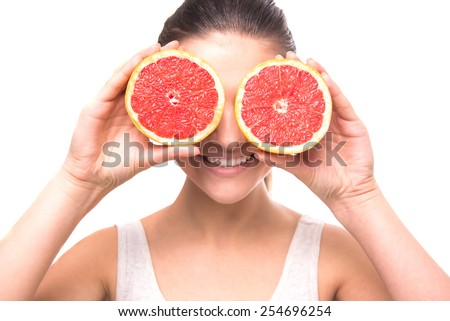 Young woman is holding slices of grapefruits to her eyes on white background.