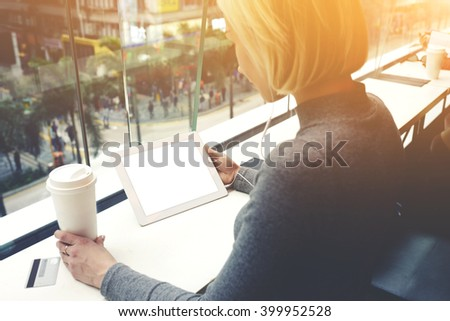 Young woman is holding touch pad with copy space screen for your text message or promotional content. Female is listening to music via digital table, while is sitting with take away coffee in cafe - stock photo