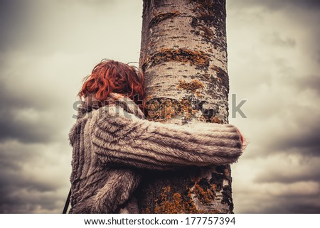 Young woman is in the park on a winter's day and is hugging a tree - stock photo