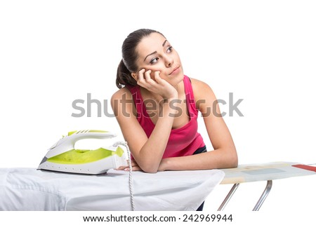 Young woman is ironing a shirt with a steam iron on white background. - stock photo