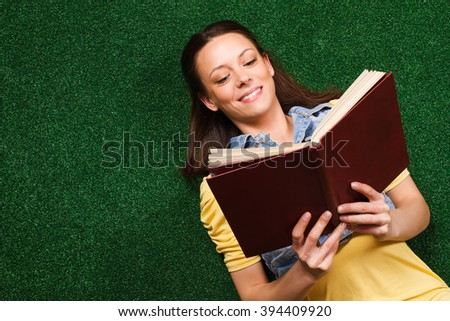 Young woman is lying down on a grass and reading  book.Woman reading book - stock photo