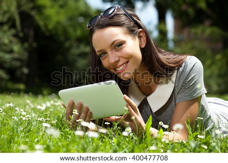 Young woman is lying in grass and using digital tablet.