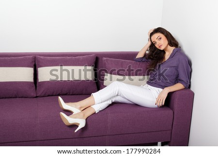 Young woman is lying on a couch .Fashion colors.
