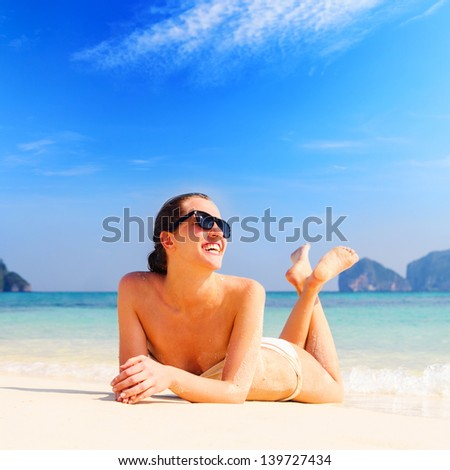 young woman is lying on beach - stock photo