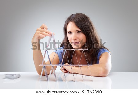 Young woman is making a house of cards 2 - stock photo