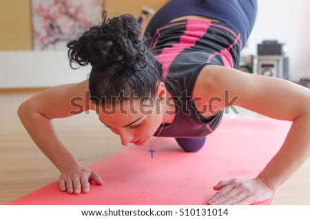 Young woman is making exercises in the hall