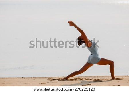 Young woman is making yoga on the beach