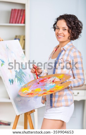 Young woman is painting a picture.