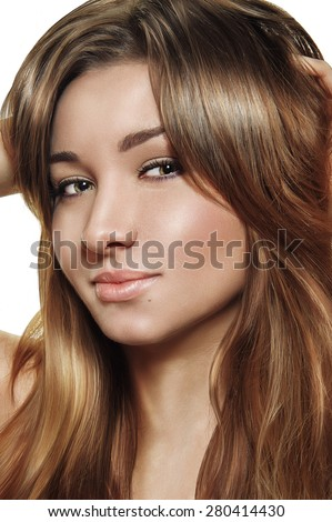 young woman is posing in the studio. She have a brown hairs, glossy lips, and smooth skin. She smiles and looking at the camera.  - stock photo