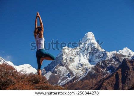Young woman is practicing yoga against Himalaya mountains - stock photo