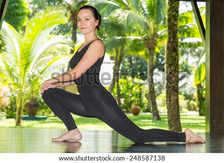 Young woman is practicing yoga and pilates on nature. Morning meditation at summer - stock photo