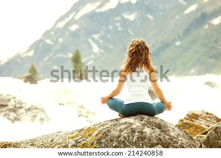 Young woman is practicing yoga at mountain river - stock photo
