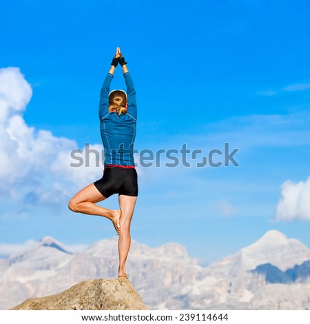 Young woman is practicing yoga high in the mountain - stock photo
