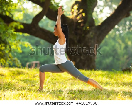 Young woman is practicing yoga outdoors on sunny day.She relaxing at the park.