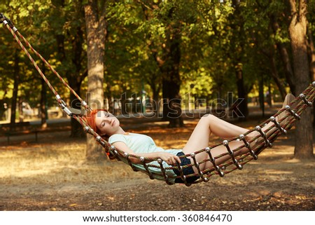 young woman is relaxing in a hammock outdoors - stock photo
