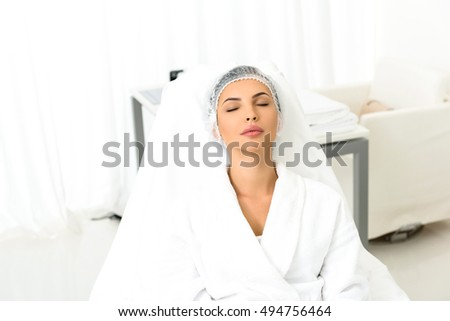 Young woman is resting after skincare procedure. She is sitting in beautician office. Her eyes are closed with pleasure