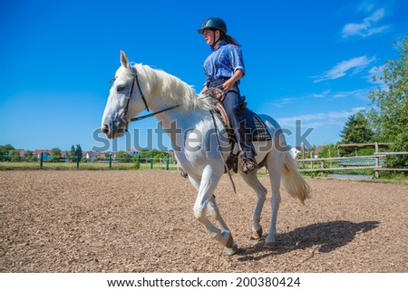 young woman is riding a white horse - stock photo
