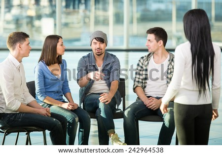 Young woman is sharing her problems with people. View of woman is telling something and gesturing while group of people are sitting in front of her and listening. - stock photo