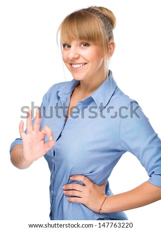 Young woman is showing OK sign, isolated over white - stock photo