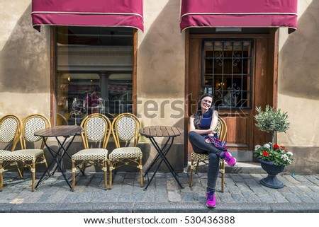 Young woman is sitting in front of the cafe